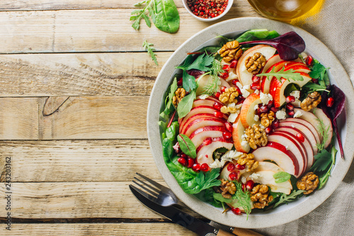Healthy multi greens salad plate with apple, walnut, pomegranate, cheese