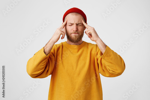Obraz The guy holds fingers on temples, his eyes are squinting, trying to remember something. Bearded man feels headache, massages his temples with fingers, isolated on a white background. - fototapety do salonu