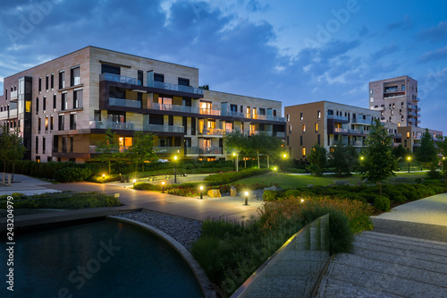 Fotografia, Obraz  Green park with modern houses in the background in the evening