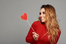 Beauty Joyful Young Fashion Model Girl With Valentine Heart Shaped  In Her Hands. Love Concept. Beautiful Smiling Young Woman On Grey Background. Space For Text