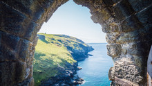 View Through The Ruins Of Tintagel Castle Of British West Landscape Coastline, Shore For Summer Holidays. Cornish Summer With Green Rocky Cliffs In Tintagel, Cornwall, UK.