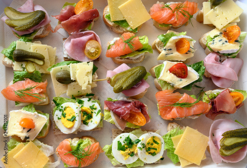 various canapes with egg, cheese, ham and salmon on a tray at the cold buffet, high angle view from above