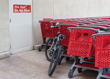 A Bicycle And Group Of Red Plastic Shopping Carts Stacked Near Outdoor Fire Escape Door. Sign With Words Fire Door Do Not Block..