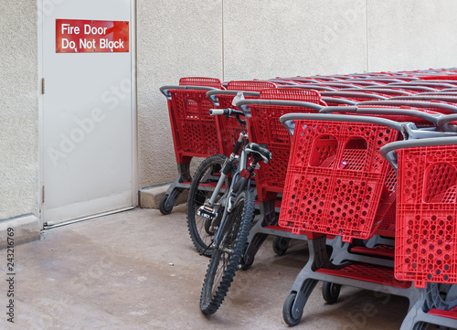 Fotografia A bicycle and group of red plastic shopping carts stacked near outdoor fire escape door