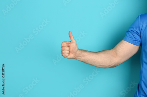 Photo Young man showing thumb sign on color background