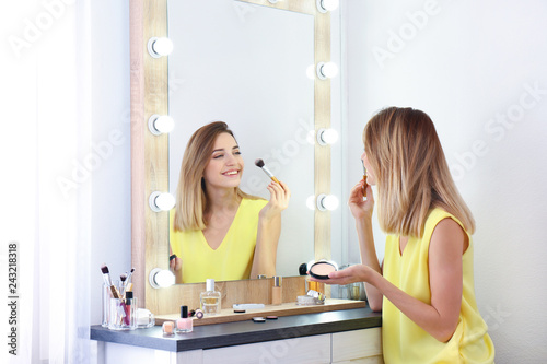 Photo Woman applying makeup near mirror with light bulbs in dressing room
