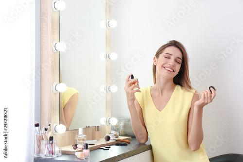 Photo  Woman applying perfume near mirror in dressing room