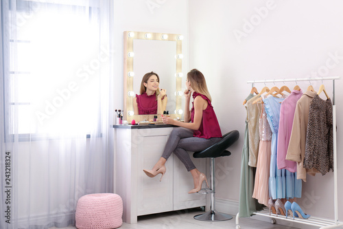 Fotografía  Woman applying makeup near mirror with light bulbs in dressing room