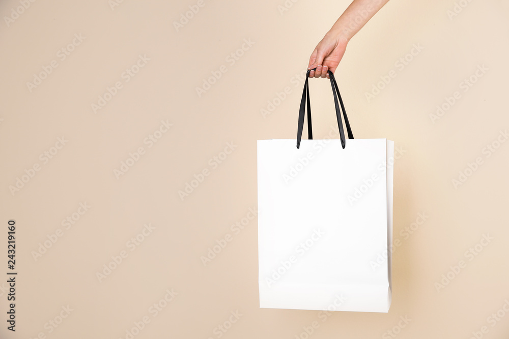 Fototapety, obrazy: Woman holding paper shopping bag on color background. Mock up for design