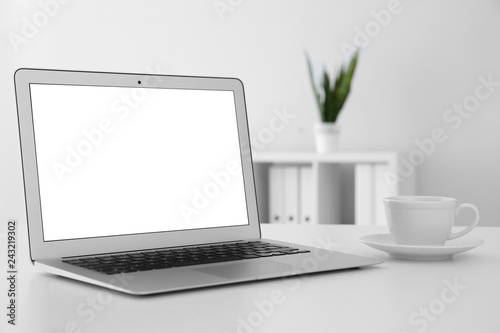 Comfortable workplace with modern laptop on table in office. Mockup for design