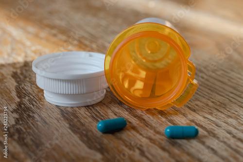 Fotografie, Obraz  Prescription pill bottle with last two blue pills spilling onto wooden kitchen table