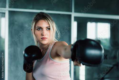 Fotomural Female boxer is training punching in fitness gym