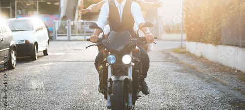 Young couple ridind motorcycle at sunset in city.