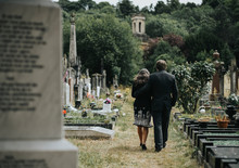 Sad Couple Walking Through A Cemetery