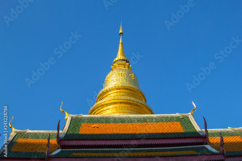 Foto  Golden pagoda and temple roof in Thai temple with blue sky background