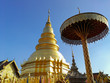 Leinwanddruck Bild - Golden pagoda and the golden umbrella with blue sky background.