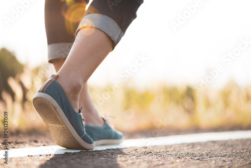 Obraz Closeup woman walking towards on the road side. Step concept. - fototapety do salonu