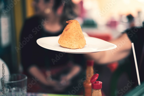 Valokuva  Person holding a plate with a coxinha