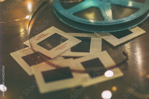Photo slides and 8mm or super 8 vintage film reel on a wood table with soft lights Canvas Print