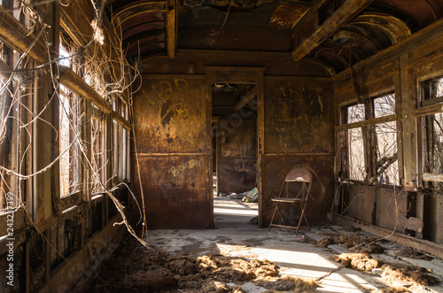 Fotoposter Oude verlaten gebouwen Interior of rusted vintage rail car with natural light coming through the windows.