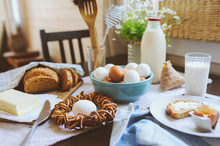 Country Breakfast On Rustic Home Kitchen With Farm Eggs, Butter, Wholegrain Bread And Milk. Organic Homemade Food, Easter Concept.
