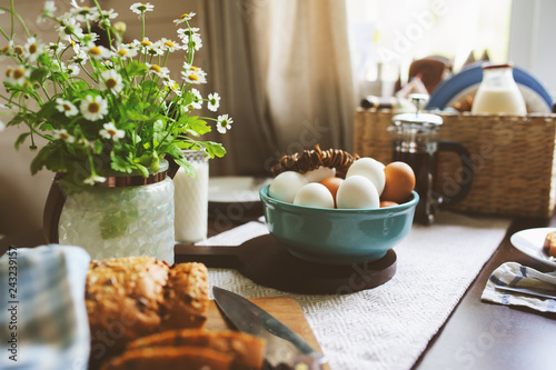 Fototapeta country breakfast on rustic home kitchen with farm eggs, butter, wholegrain bread and milk. Organic homemade food, easter concept. obraz
