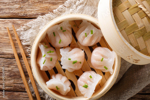 Dim Sum in bamboo steamer, Chinese cuisine. Closeup rustic. Horizontal top view