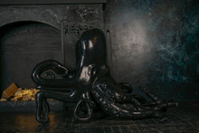 Scary Octopus Chair On The Background Of A Black Large Fireplace With White Candles In A Gothic Luxury Room. Nobody.