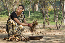 Smiling Rural Woman Dressed In Saree Collecting Dried Leaves From Ground In An Iron Gold Pan.