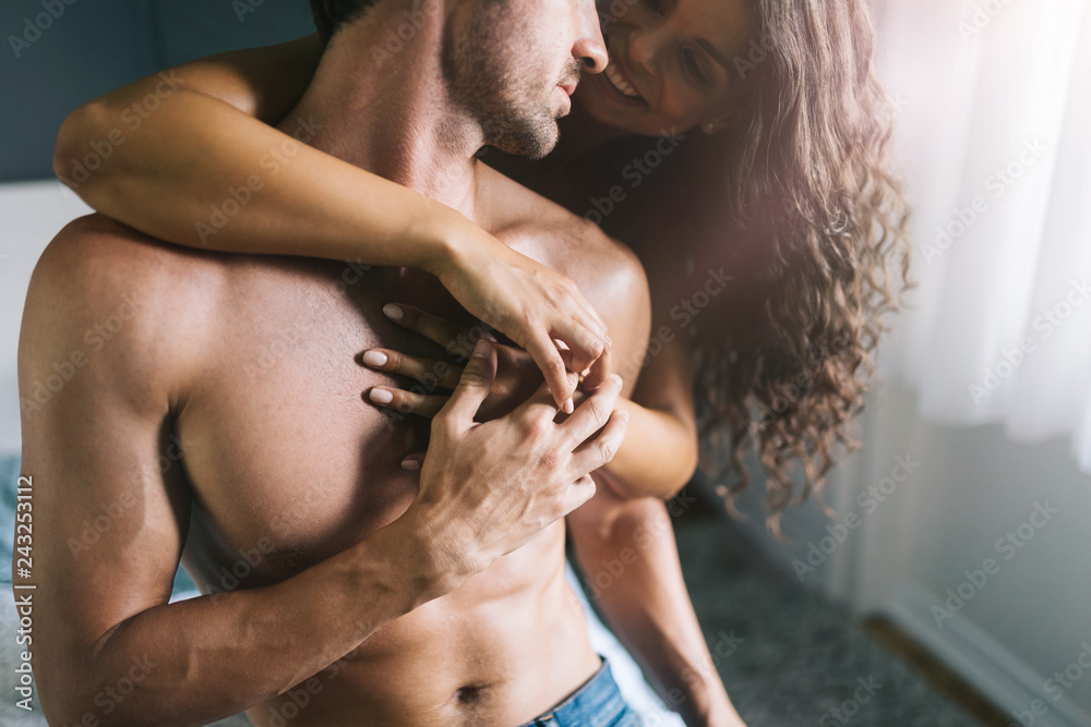 Fototapeta Romantic young couple being intimate and sensual in bedroom