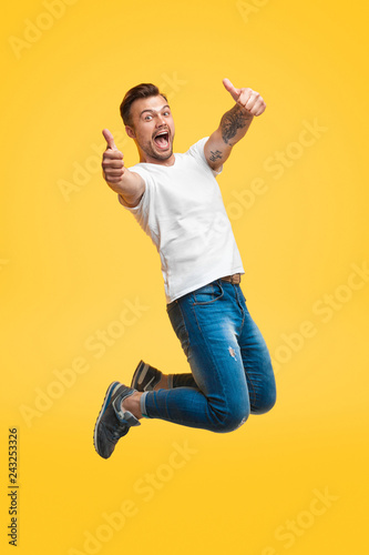 Fotografia Excited man jumping and gesturing thumb up