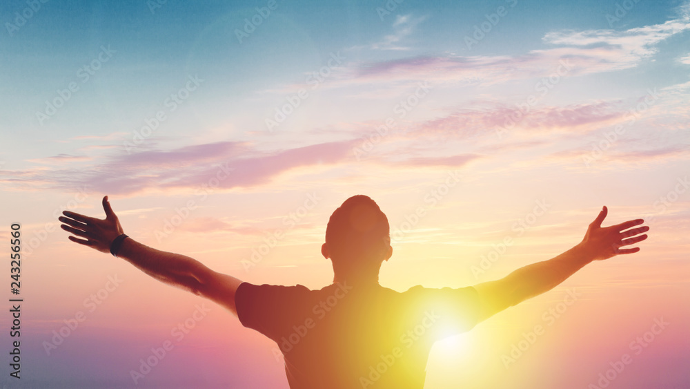 Fototapeta Young man standing outstretched at sunset. Victory
