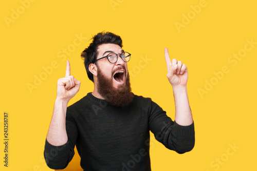 Portrait of amazed bearded man pointing up over yellow background