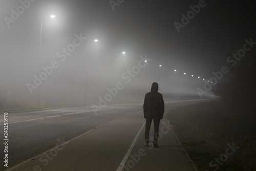 Canvas Print Young man alone slowly walking under white street lights in night