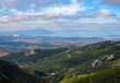 Panoramic view from above on the forests and the village on serpentine of the Greek island of Evia with the sea and clouds on the horizon on a sunny day