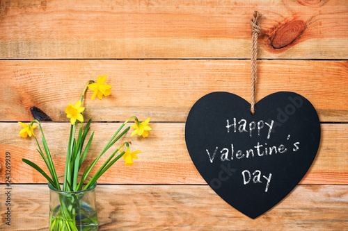Papiers peints Affiche vintage Happy valentine's day written on a chalkboard in the shape of a heart, daffodils and wooden planks background