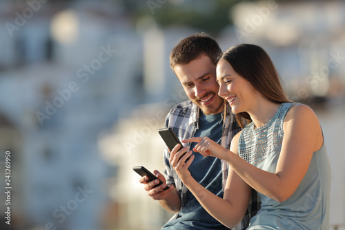Happy couple sharing phone content in a town