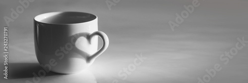 Heart shaped shadow on a coffee cup, black and white