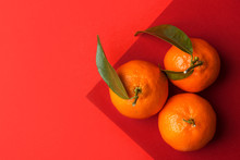 Three Ripe Bright Raw Tangerines On Branch With Green Leaves On Graphic Duotone Orange Red Crimson Background. Chinese New Year Prosperity Luck Concept. Clean Minimalist Style. Top View Copy Space
