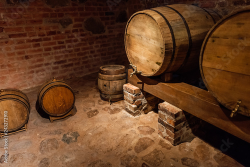 Fotografie, Obraz  Wine barrels stacked in the old cellar of the winery