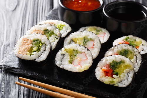 Futomaki rolls with various fillings are served with sauces close-up on a slate board. horizontal
