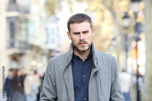 Fototapeta Angry man walking in the street looking at camera