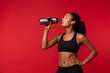 Image of healthy african american woman in black sportswear holding water bottle, isolated over red background