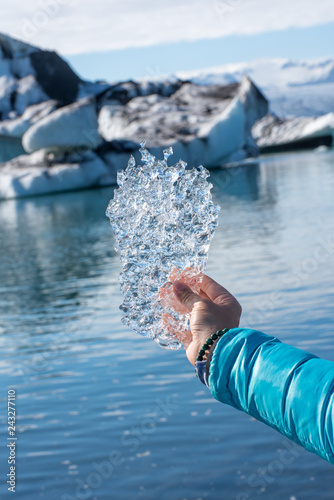 Fotografie, Obraz  Transparent piece of ice in hand on background of ocean