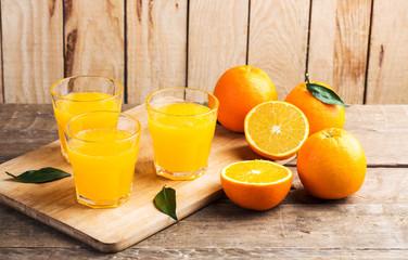 Orange juice. Glasses of orange juice and fruits against wooden background