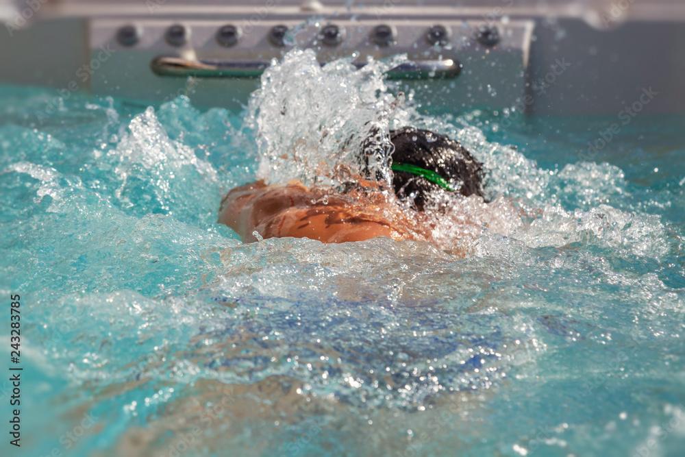 Fototapeta man swimming crawl against the tide in a hot tub