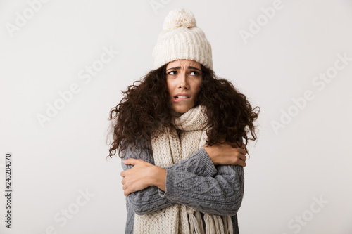 Fotomural  Upset young woman wearing winter scarf