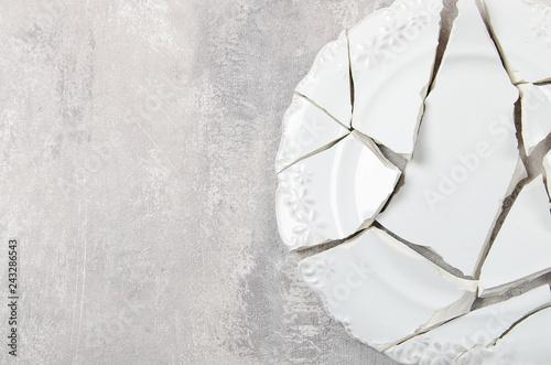 Fotografie, Obraz  broken porcelain plate on old grey background. Copy space