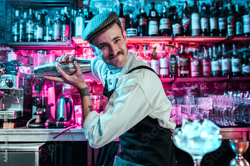 Photo Expert barman is making cocktail at night club or bar