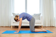 fitness, yoga and healthy lifestyle concept - woman doing cat pose on mats at home